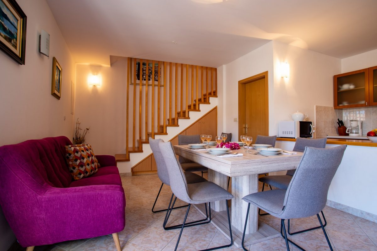 Stylish and modern dining and living room with a served dining table in the Villa Bonaca